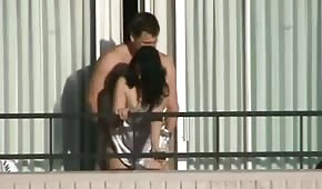He's fucking her from behind on the balcony