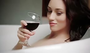 Chick drinks wine and caresses while bathing