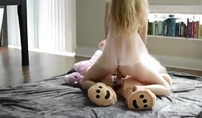 A neat blonde riding a teddy bear