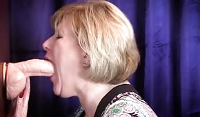 The mature lady is choking on a rubber cock