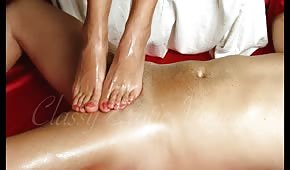 Oiled lady massages the cock with her feet