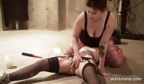 Domina is pouring wax onto the naughty blonde's body