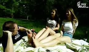 The guy licked the young feet in the park