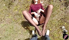 The chick massages the cock with her feet outdoors